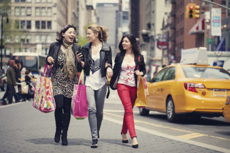 Happy shopping friends socializing walking on NYC street