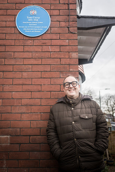 Comedian Justin Moorhouse in front of the Tom Curry plaque