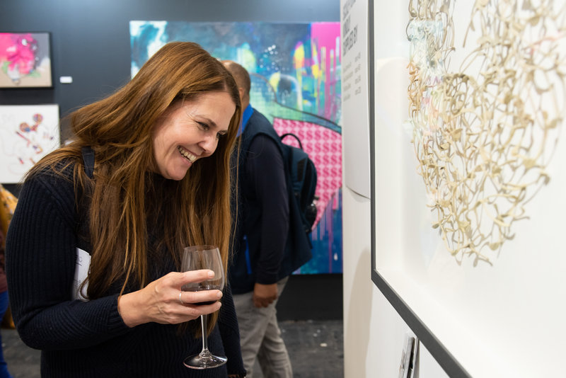 Woman observing artwork at Manchester Art Fair