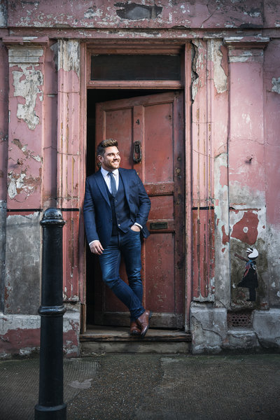Mark Kingswood singer posing by a door wearing a suit.